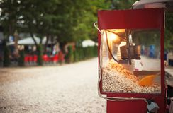 Popcorn in Park. Details of a device for popcorn, blurry background of public park stock photo