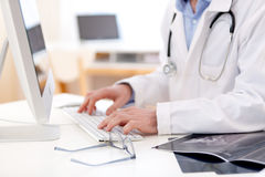 Details of doctor hands typing on keyboard. View of Details of doctor hands typing on keyboard Royalty Free Stock Photo