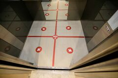 Details with an elevator floor segmented in four places to stand for social distancing during the covid-19 outbreak