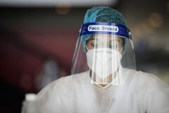 Details with the face of a health official taking Covid-19 test, with mask and face shield