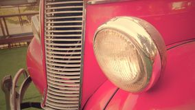 Details of the front headlight lamp pink vintage classic car Royalty Free Stock Images