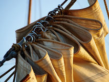 Details of gathered sail of a large sailing ship. Details of gathered sail of a large classical traditional vintage tall sailing ship Royalty Free Stock Images