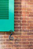 Details of green  window shutters and holder on brick wall Stock Photos