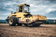 Details of highway construction site - industrial machinery, vibratory soil compactor working Stock Photography