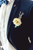 Details of male wedding clothes. Beautiful boutonniere pinned on man in blue suit, white shirt and blue bow tie. Royalty Free Stock Images