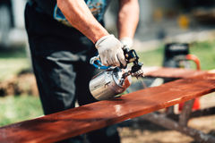Details of man using spray gun or airbrush for painting  fence. Carpentry details with woodwork and handyman Stock Images
