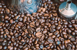 Details of a metal coffee maker in coffee beans. Coffee pot surrounded by roasted coffee beans Royalty Free Stock Image