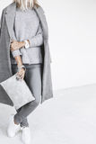 Details of minimalistic fashion outfit. Unrecognizable model wearing casual outfit and holding clutch bag. Gray clothing in trendy minimalistic style. Street Stock Photos