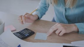 Details. modern office, female hands close-up, a girl counts on a calculator and makes notes in a notebook 4K