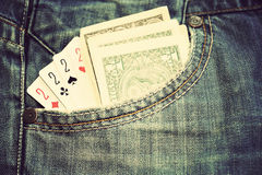Details of one dollars banknotes and poker cards in pocket. Jeans Stock Photos