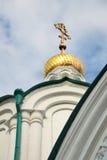 Details of orthodox cathedral, bottom view. White walls of orthodox cathedral, golden cupola with cross against blue cloudy sky, Svyatogorskaya Svyato-Uspenskaya Stock Images