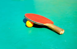 Details of pingpong table with playing equipment and yellow ball. Details of pingpong table with playing equipment and yellow ball Stock Photos