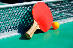 Details of pingpong table with playing equipment and yellow ball. Details of pingpong table with playing equipment and yellow ball Stock Photography