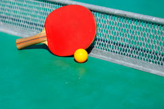 Details of pingpong table with playing equipment and yellow ball. Details of pingpong table with playing equipment and yellow ball Stock Photo