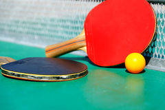Details of pingpong table with playing equipment and yellow ball. Details of pingpong table with playing equipment and yellow ball Royalty Free Stock Images