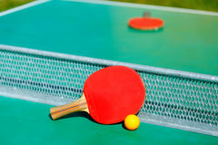 Details of pingpong table with playing equipment and yellow ball. Royalty Free Stock Photo