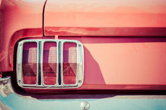 Details of a red boot, red tail light and chrome plated bumper Stock Photo