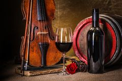 Red wine in glass, barell and violin stock photo