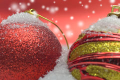 Details from a setup with colorful christmas globes. On red snowy background Stock Photography