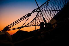 Details and silhouettes of the bow from an old sailing ship at s. Ropes, nets, cables, pulleys and bollards as shadows against a colorful sky of red and blue royalty free stock images