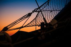 Details and silhouettes of the bow from an old sailing ship at s. Ropes, nets, cables, pulleys and bollards as shadows against a colorful sky of red and blue stock image