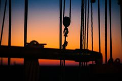Details and silhouettes of an old sailing ship at sunset. Ropes, nets, cables, pulleys and bollards as shadows against a colorful sky of red and blue colors of royalty free stock image
