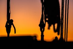 Details and silhouettes of an old sailing ship at sunset. Ropes, nets, cables, pulleys and bollards as shadows against a colorful sky of red and blue colors of stock image