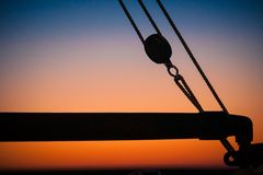 Details and silhouettes of an old sailing ship at sunset. Ropes, nets, cables, pulleys and bollards as shadows against a colorful sky of red and blue colors of stock photo