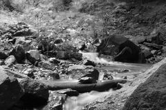 Stream flowing in countryside. Black and white view or stream flowing past rocks in countryside Stock Images