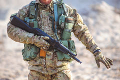 Details of soldier in tactical gear with a gun in his hand. The gun in the hands of soldier and other tactical equipment in training outdoor Royalty Free Stock Photos