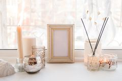 Details of still life in the home interior. Aroma stick, interior items, candles, frame for text, Moody. Cosy autumn winter light. Concept. Copy space stock images