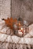 Warm sweater on wooden rustic bench, Candle, Quiet cozy homely scene. Fall autumn weekend. Monochrome concept, vertical. Details of still life in the home stock photos