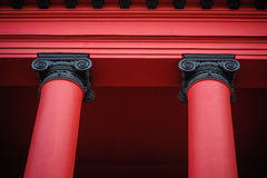 Details of two beautiful red columns supporting roof of old red building Stock Images