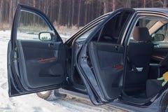 Details van de zwarte auto in de cabine, het stuurwiel, de boomstam, de snelheidsmeter en de open deuren royalty-vrije stock foto