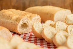 Details von Laiben über roter und weißer Kontrolleurtischdecke mit Brotscheiben Lizenzfreies Stockfoto