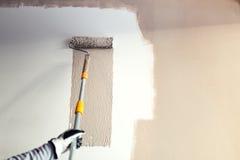Details von Malereiwänden, Industriearbeiter, der Rolle und andere Werkzeuge für das Malen von Wänden verwendet stockbilder
