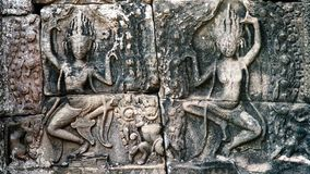 Details of a wall in an old temple in Angkor Wat. Dancing Apsaras an old Khmer art carvings on the wall in Angkor Wat temple near Siem Reap town, Cambodia Stock Photos