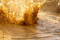 Details of water drops in mud from a splash in a puddle in an obstacle race stock images