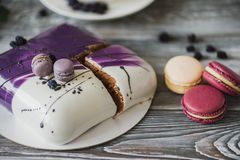Details of a wedding or a birthday purple cake, in studio on wooden background. Purple small macarons as main decoration.  Royalty Free Stock Photo