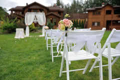 Details of wedding ceremony. On green lawn decorated with bouquet white chairs living for your wedding ceremony outdoors Stock Photos