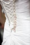 Details of wedding dress. Close up of lace corset with beading on back of wedding dress in daylight royalty free stock image