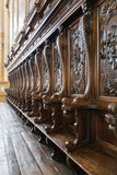 Details of wooden pews next to the altar of a medieval church. Royalty Free Stock Photos