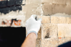 Details of worker hands using cement and stone. Construction mason worker at work Royalty Free Stock Images