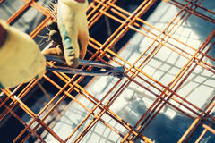 Details with worker using wire rod and pliers for securing reinforcement steel bars on house building Royalty Free Stock Image
