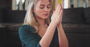 Detailsportret van de meditatie van de blondevrouw in ochtendyoga het praktizeren voor een gezonde levensstijl, thuis in het leve stock video