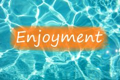 Detal of word `Enjoyment` on swimming pool water and sun reflecting on the surface.  Stock Photos