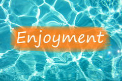 Detal of word & x22;Enjoyment& x22; on swimming pool water and sun reflecting on the surface Royalty Free Stock Images