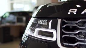 Detalhe ascendente próximo para um dos faróis do diodo emissor de luz de um carro preto moderno estoque Detalhe exterior, farol d vídeos de arquivo