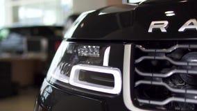 Detalhe ascendente próximo para um dos faróis do diodo emissor de luz de um carro preto moderno estoque Detalhe exterior, farol d filme