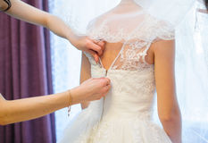 Detalhe da asseguração do vestido da noiva foto de stock royalty free